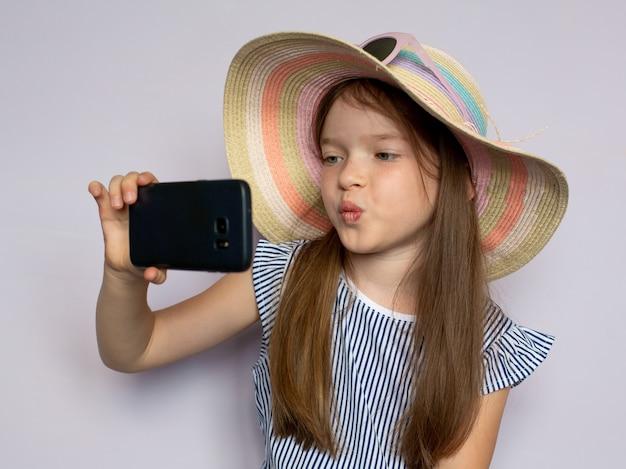 Schattig mooi klein meisje in een jurk en hoed maakt foto 's maakt selfie met een smartphone Premium Foto