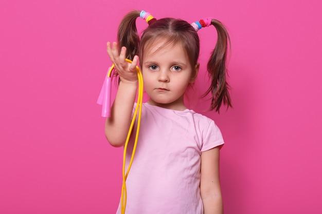Schattig, verdrietig meisje houdt in de hand springtouw. klein kind wil met iemand spelen. schattige jongen met paardenstaarten en kleurrijke scrunchies, draagt t-shirt op roos. Gratis Foto