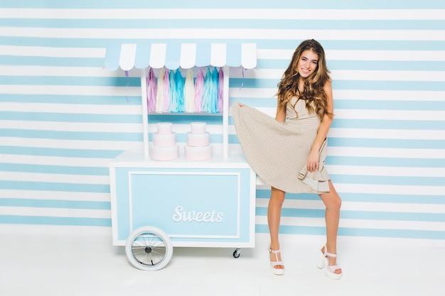 Schattig vrolijk meisje speelt met haar stijlvolle jurk staande naast toonbank met snoep. charmante slanke jonge vrouw in trendy witte sandalen dansen op gestreepte muur met glimlach. Gratis Foto