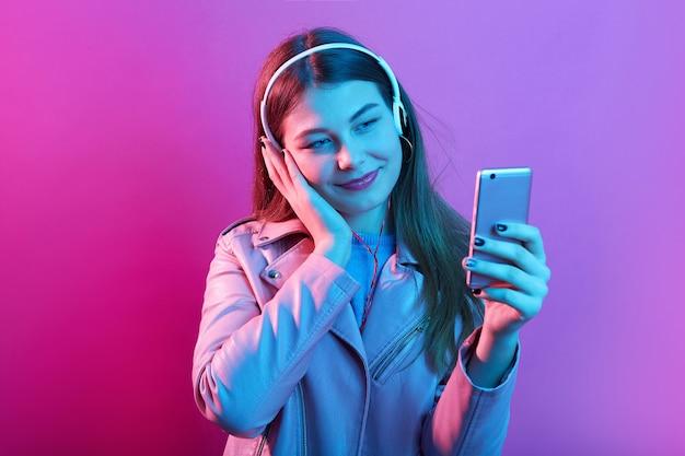 Schattige aantrekkelijke tienermeisje luisteren muziek in koptelefoon geïsoleerd over roze neon ruimte, raakt haar oor, slimme telefoon scherm kijken Premium Foto