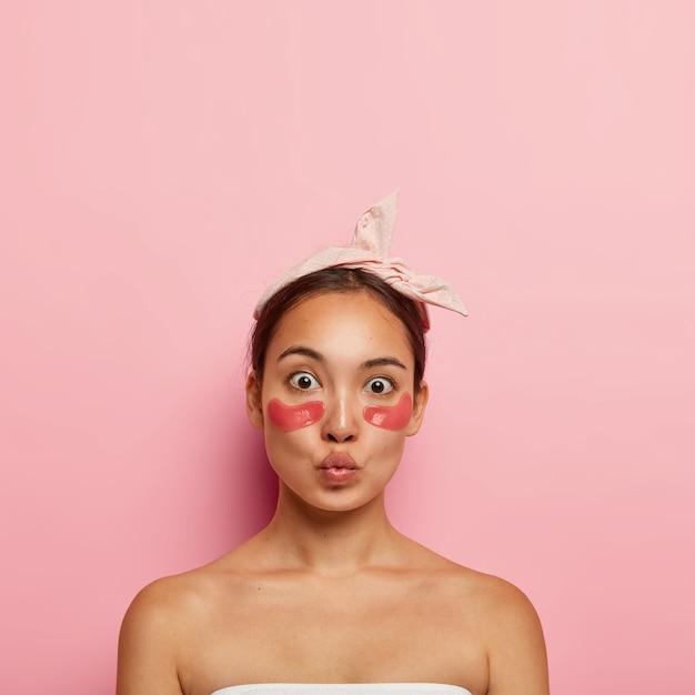 Schattige aziatische vrouw past zelfklevende pleisters onder de ogen toe om wallen en donkere kringen te verminderen, draagt een hoofdband op het hoofd, houdt de lippen gevouwen, staat blote schouders, geïsoleerd op een roze muur Gratis Foto