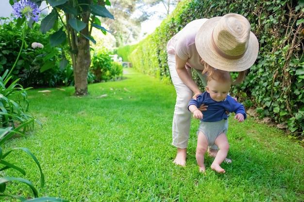 Schattige baby in blauw shirt eerste stappen met hulp van moeder en glimlachen. jonge moeder in de zuigeling van de hoedenholding op gras. eerste stappen op blote voeten Gratis Foto
