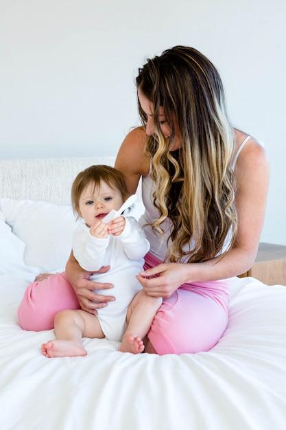 Schattige baby spelen met een kam zittend op een bed met een brunette vrouw Premium Foto