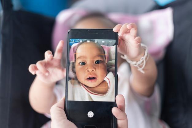Schattige baby toont zijn eigen foto's op de smartphone op de kinderwagen. Premium Foto