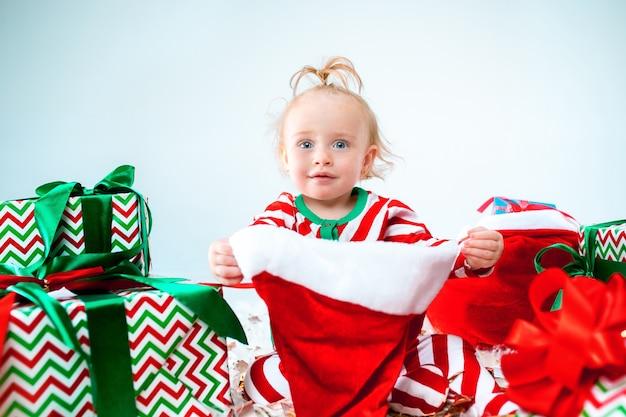 Schattige babymeisje dragen kerstmuts poseren over kerstversiering met geschenken. zittend op de vloer met kerstbal. vakantie seizoen. Gratis Foto