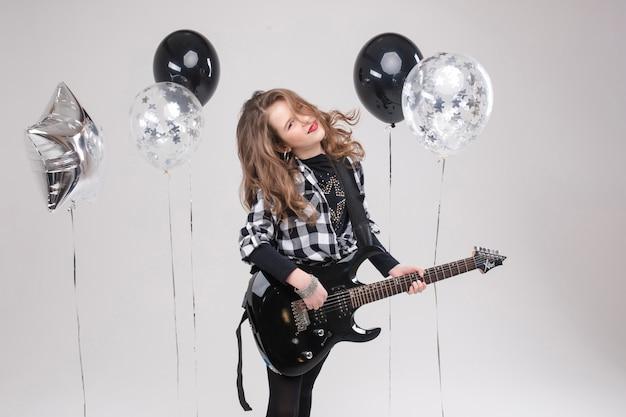 Schattige babymeisje rockster spelen elektrische gitaar en zingen lied omgeven door ballonnen Premium Foto