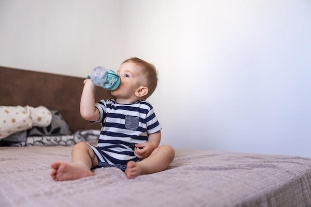 Schattige blonde jongere zittend op het bed in de slaapkamer en drinkwater uit zijn fles. Premium Foto