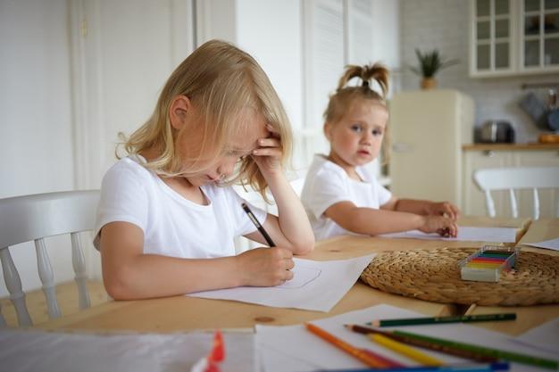 Schattige blonde kleine jongen huiswerk, pen vasthouden, iets tekenen op een vel papier met zijn mooie zusje zittend op de achtergrond. twee kinderen maken van tekeningen aan houten tafel in de keuken Gratis Foto