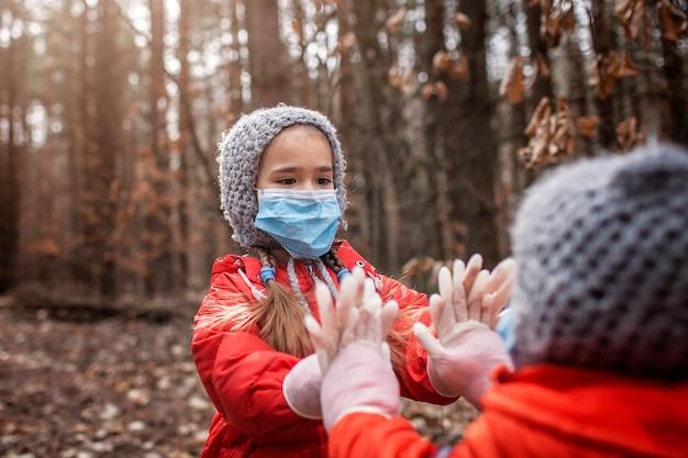 Schattige broer of zus in rode jassen met gasmaskers en medische handschoenen die pasteitaart spelen Premium Foto