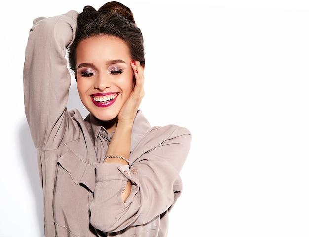 Schattige brunette vrouw model in casual beige kleding met lichte make-up en rode lippen Gratis Foto