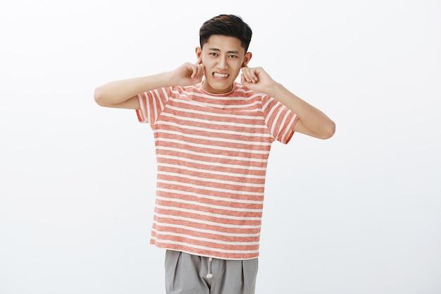 Schattige chinese man die niet gewend is aan het drukke stadsleven oren sluiten met wijsvinger hoort geen luid geluid van files tanden op elkaar klemmen ontevreden Gratis Foto