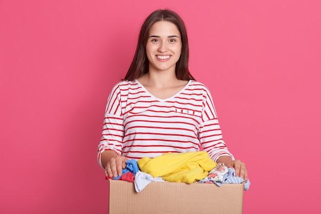 Schattige dame draagt casual kleding poseren geïsoleerd over roze studio muur Premium Foto