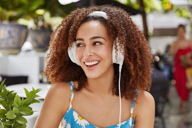 Schattige donkere vrouw met vrolijke uitdrukking kijkt vrolijk weg Gratis Foto