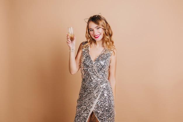 Schattige europese vrouw met rode lippen champagne drinken, kerst vieren op feestje Gratis Foto