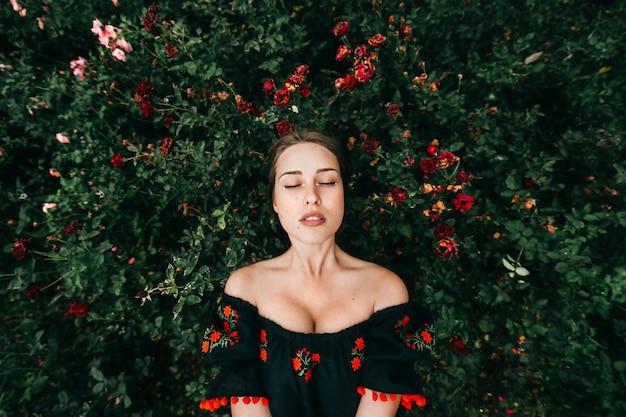 Schattige fantastische jonge vrouw in geborduurde jurk met gesloten ogen Premium Foto