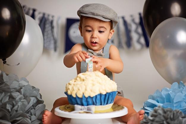 Schattige gelukkige babyjongen met een cake om een verjaardag te vieren Premium Foto