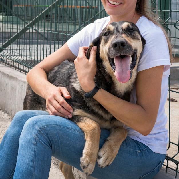 Schattige hond spelen met vrouw in opvangcentrum voor adoptie Gratis Foto