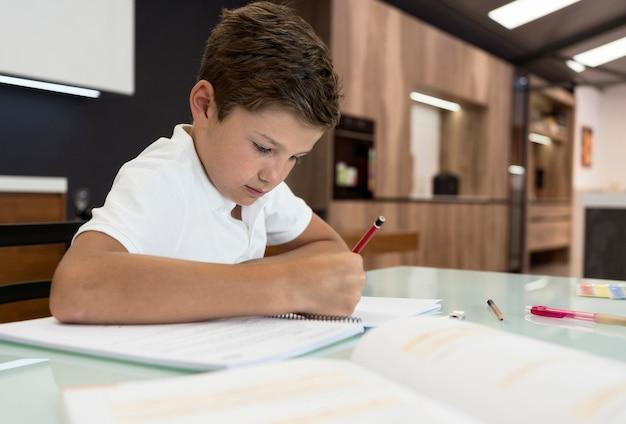 Schattige jonge jongen die zijn huiswerk doet Gratis Foto