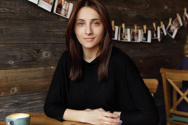 Schattige jonge kaukasische brunette vrouw met losse kapsel handen rusten op tafel terwijl u geniet van haar vrije dag, ontspannen in café tijdens koffiepauze, wachten op vriend, op zoek met glimlach Gratis Foto