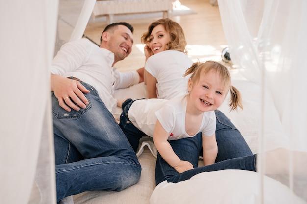 Schattige jongen dochter en vader kietelen moeder plezier goede tijd samen spelen thuis, gelukkige ouders en klein kind meisje genieten van grappige activiteit en communicatie, familie lachen ontspannen Premium Foto