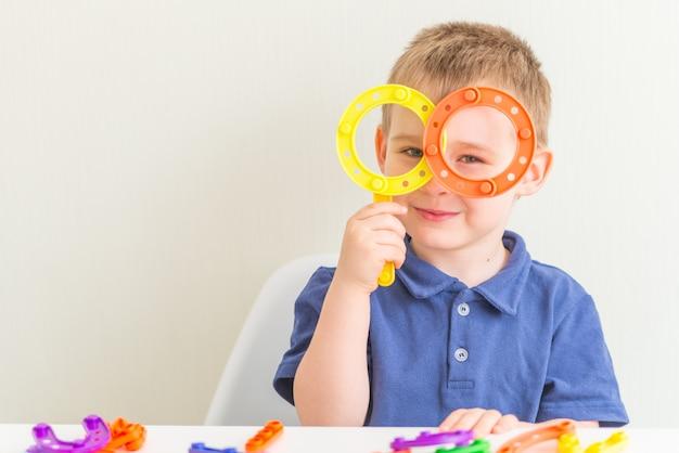 Schattige jongen gemaakt glazen plastic blok speelgoed en glimlachen. ruimte kopiëren. horizontale foto van grappige peuter Premium Foto