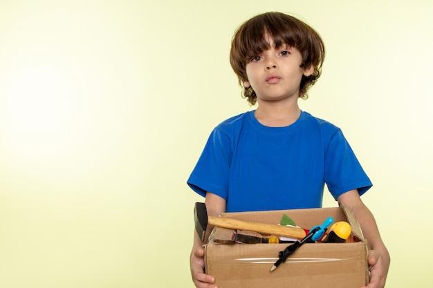 Schattige jongen in blauw t-shirt met doos met gereedschap op witte muur Gratis Foto