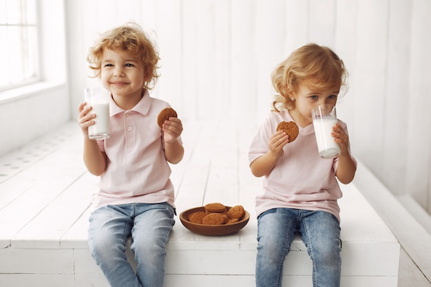Schattige kinderen eten koekjes en consumptiemelk Gratis Foto