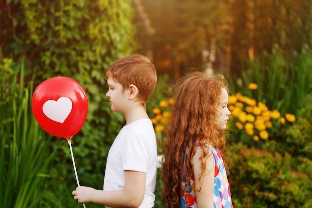 Schattige kinderen houden rode ballonnen met hart in de zomer park. Premium Foto