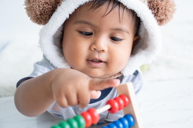 Schattige kleine asin babyjongen spelen met houten speelgoed Premium Foto