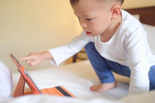 Schattige kleine aziatische 2-3 jaar oude peuter jongen kind zit in bed kijken naar een video van tablet pc Premium Foto