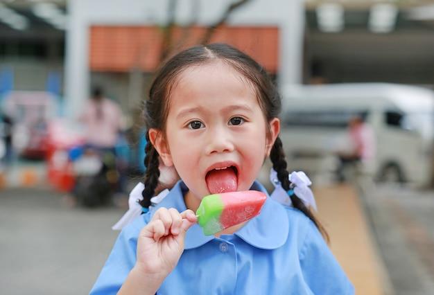 Schattige kleine aziatische kind meisje in schooluniform geniet van het eten van ijs in het park. Premium Foto