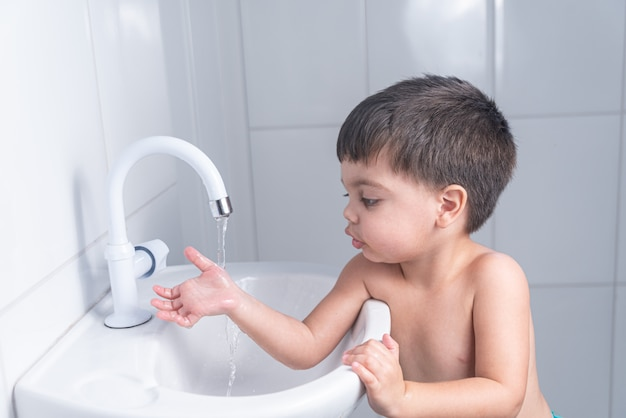 Schattige kleine babyjongen hand wassen in de badkamer wastafel Gratis Foto