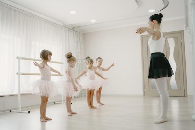 Schattige kleine ballerina's in roze balletkostuum. kinderen in spitzen dansen in de kamer. kind in dansles met teatcher. Gratis Foto