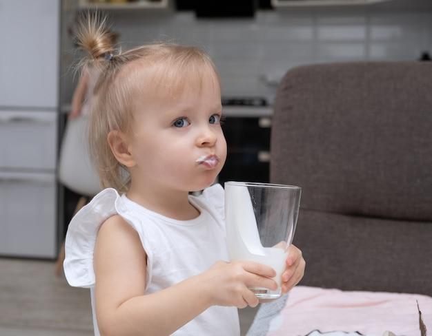 Schattige kleine blonde meisje biologische melk drinken, glas thuis keuken houden Premium Foto