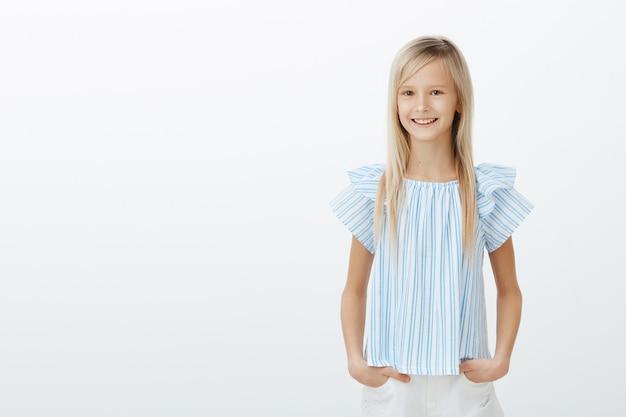 Schattige kleine dame winkelen met moeder. blij gelukkig vrouwelijk kind in blauwe blouse, hand in hand op de heupen en breed glimlachend, verbaasd, plezier maken met vrienden over grijze muur Gratis Foto