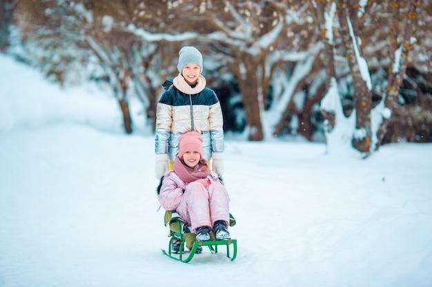 Schattige kleine gelukkige meisjes die in de winter sneeuwdag rodelen. Premium Foto