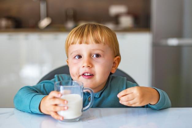 Schattige kleine jongen consumptiemelk of yoghurt en karamel eten tijdens het ontbijt in de keuken in de ochtend Premium Foto