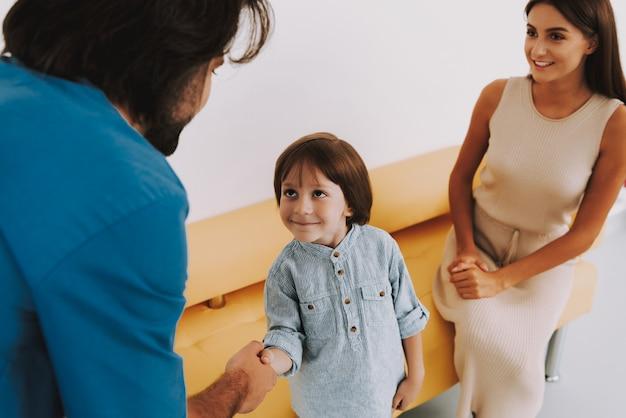 Schattige kleine jongen lacht naar arts en handshaking Premium Foto