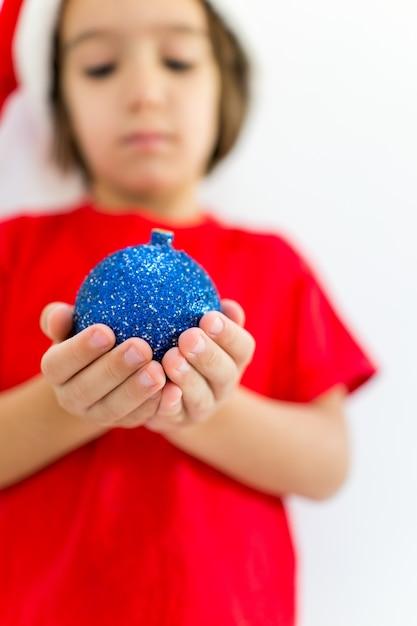 Schattige kleine jongen met decoratie bal dragen kerstmuts en glimlachen Premium Foto