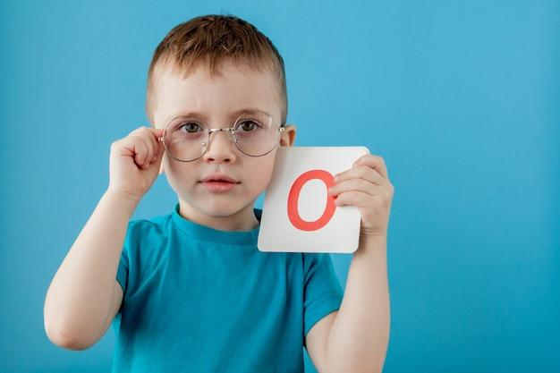 Schattige kleine jongen met letter. kind leert brieven. alfabet Premium Foto
