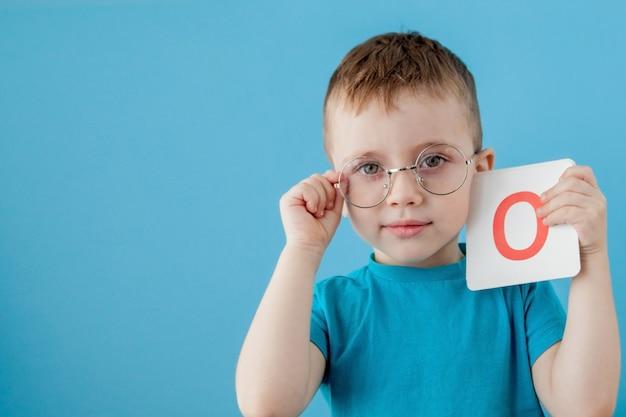 Schattige kleine jongen met letter op blauwe muur. kind dat brieven leert. alfabet Premium Foto