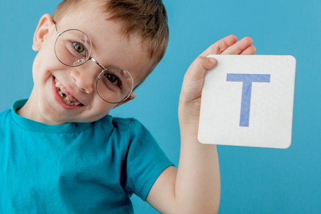 Schattige kleine jongen met letter op blauwe muur. kind leert brieven. alfabet Premium Foto