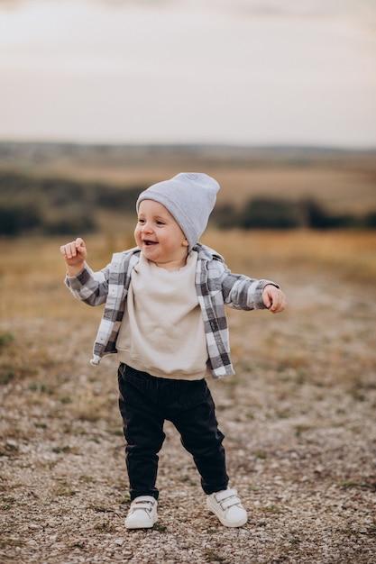 Schattige kleine jongen met plezier in het veld Gratis Foto