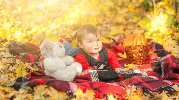 Schattige kleine jongen met teddybeer zittend op een deken Gratis Foto