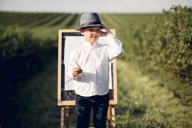 Schattige kleine jongen schilderij in een park Gratis Foto