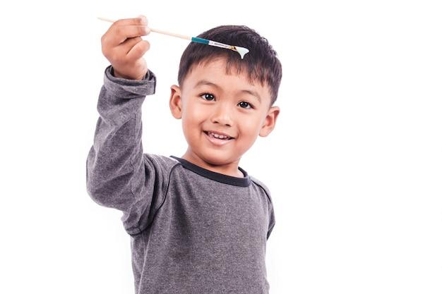 Schattige kleine jongen spelen penseel Premium Foto