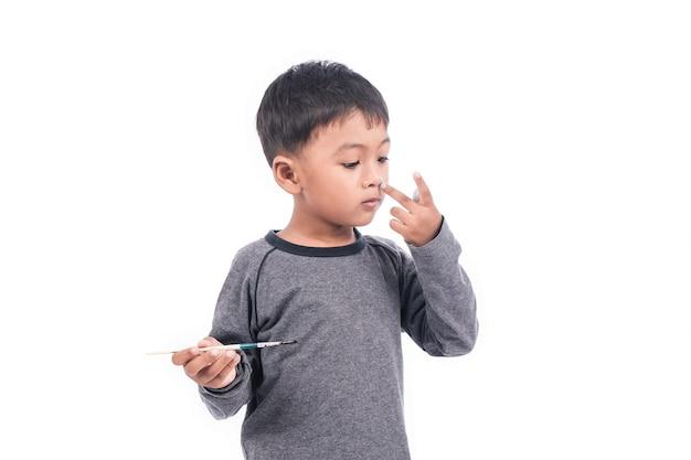Schattige kleine jongen spelen schilderij op de neus Premium Foto
