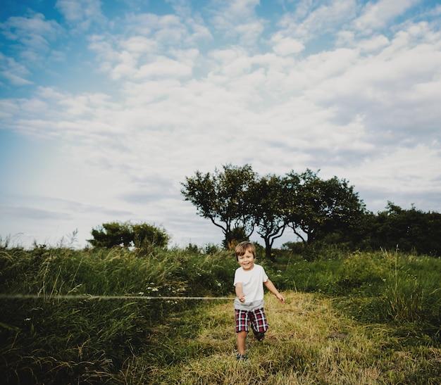 Schattige kleine jongen staat op een groen veld in de stralen van de avond Gratis Foto