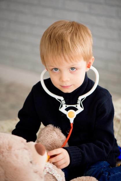 Schattige kleine jongen verkleed als arts spelen met speelgoed thuis dragen. Premium Foto