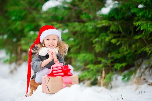 Schattige kleine kabouter met kerstcadeau cadeau in de winter buiten op kerstavond Premium Foto